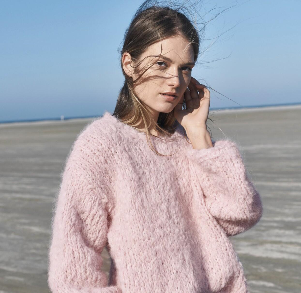 Kvinna i den fluffiga rosa tröjan på en blåsig strand.