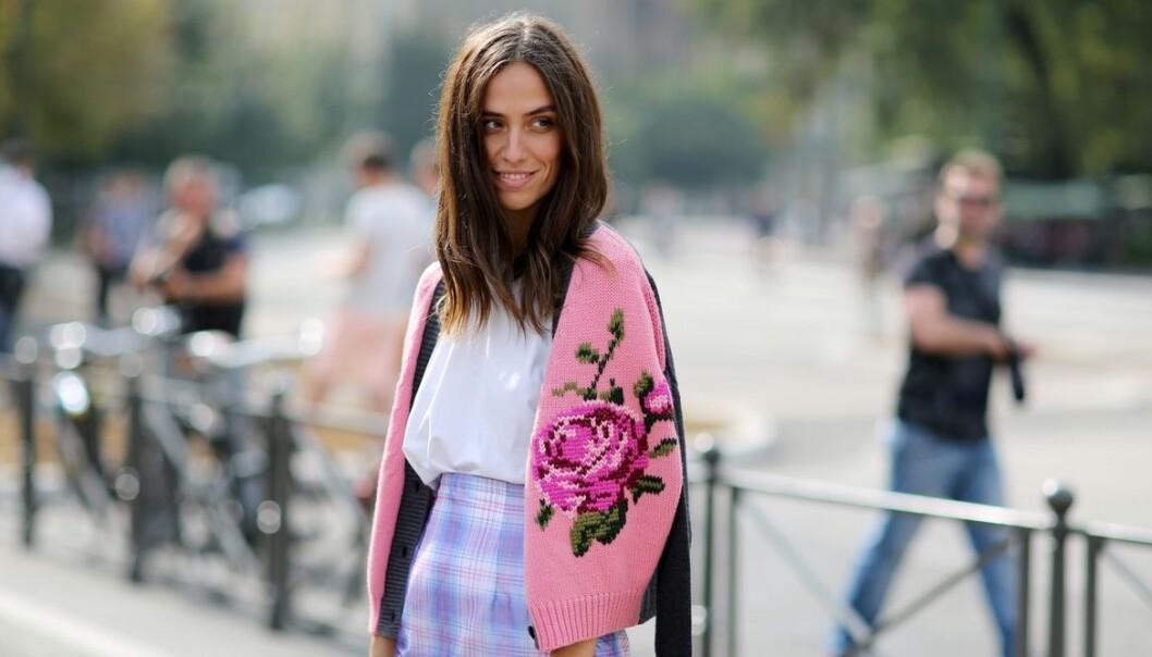 Kvinna i stickad tröja med en stor ros.