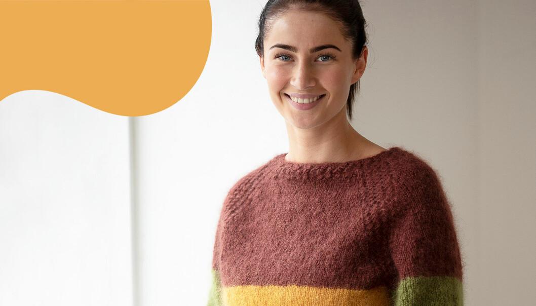 Kvinna i klädd stickad tröja i höstfärger ler mot kameran