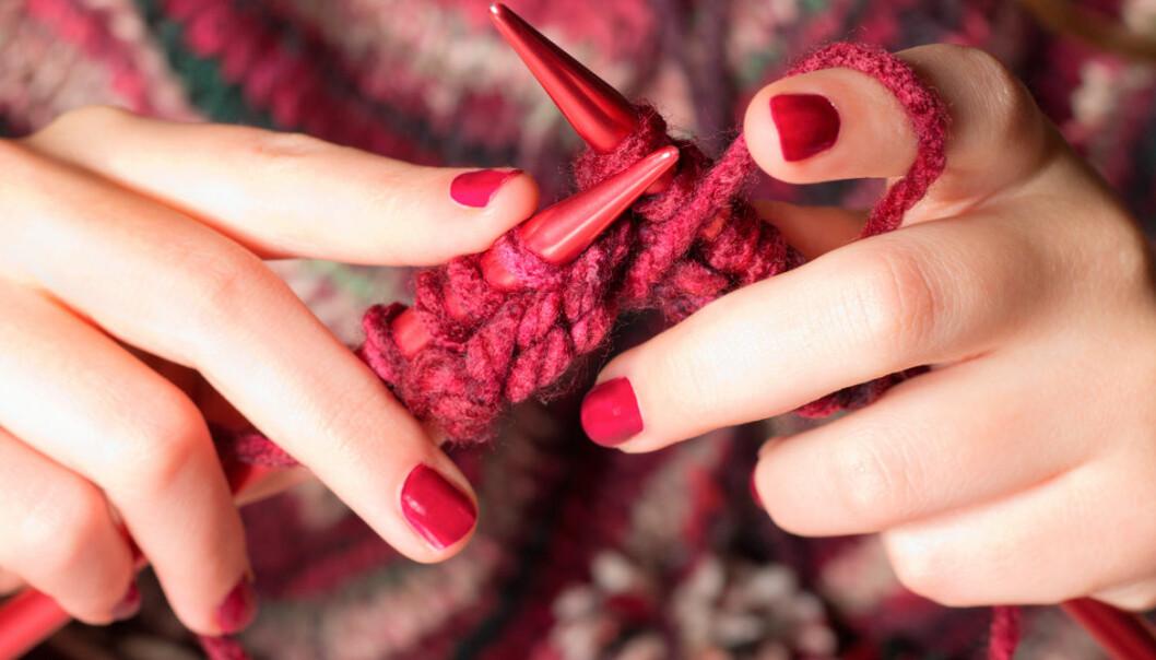 Bild på händer med rött nagellack som stickar med rött garn.