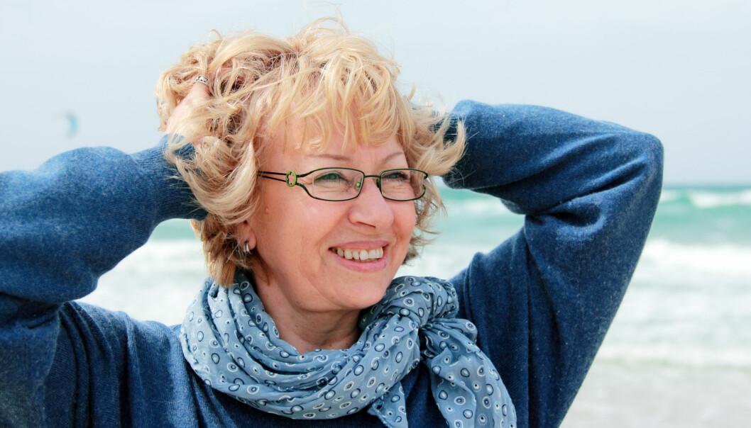 Glatt leende kvinna i 65-årsåldern står vid havet.