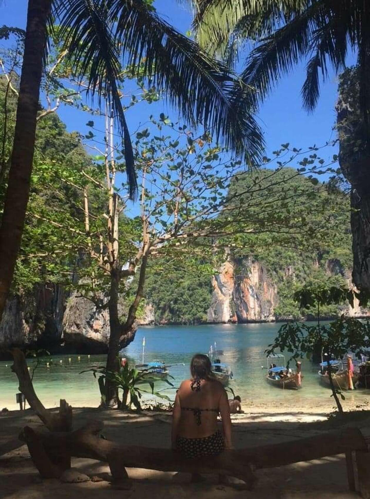 Susanne Bohlin på en Thailändsk strand med palmer, blå himmel och klippor.
