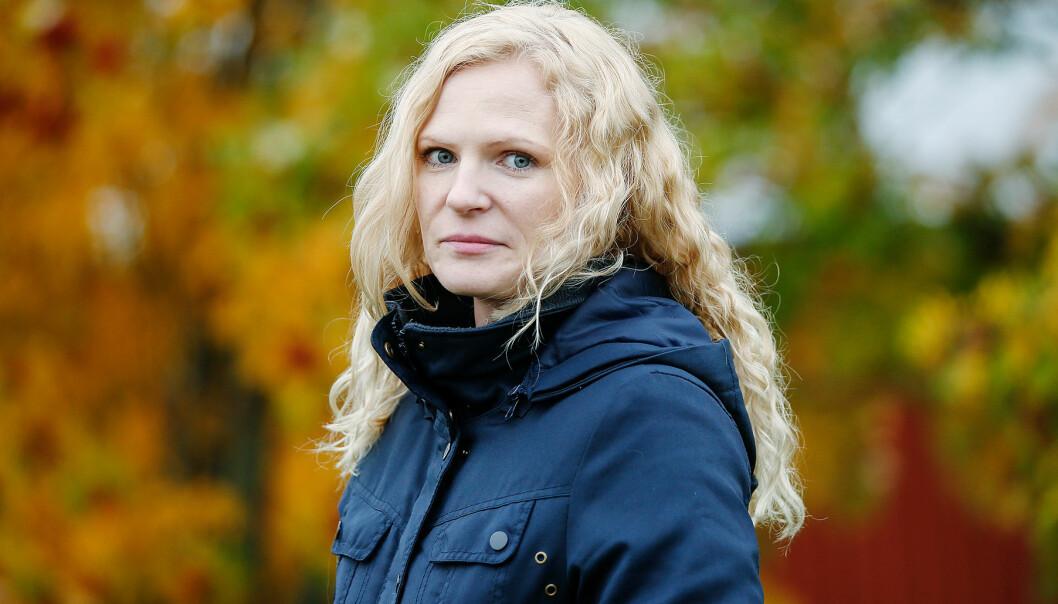Susanne tittar in i kameran med höstlöv i bakgrunden