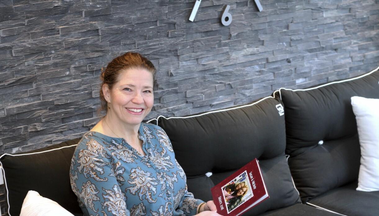 Susan sitter hemma i soffan med en minnesbok i knät som har en bild av henne och systern på framsidan när de möts på flygplatsen.