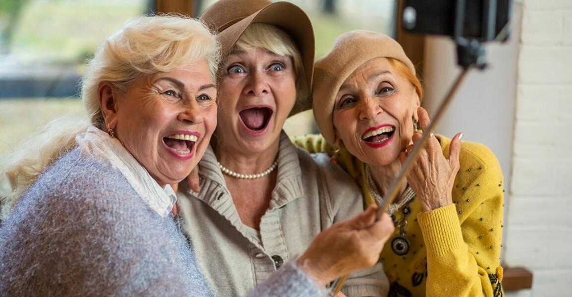 Tre glada tanter ler mot en mobilkamera
