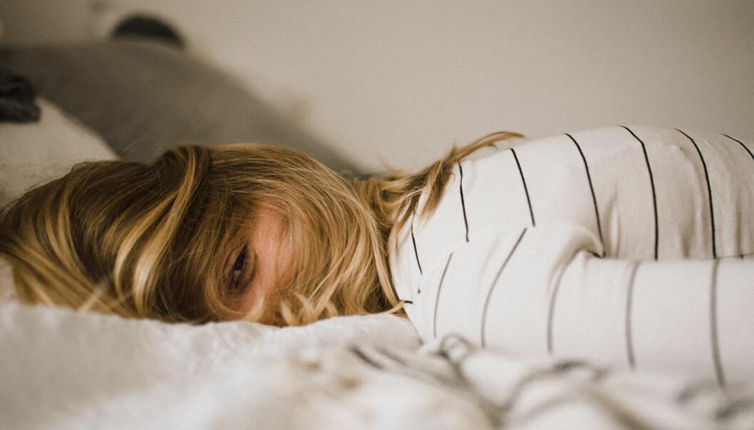 Kvinnor ligger sömnlös i sängen.