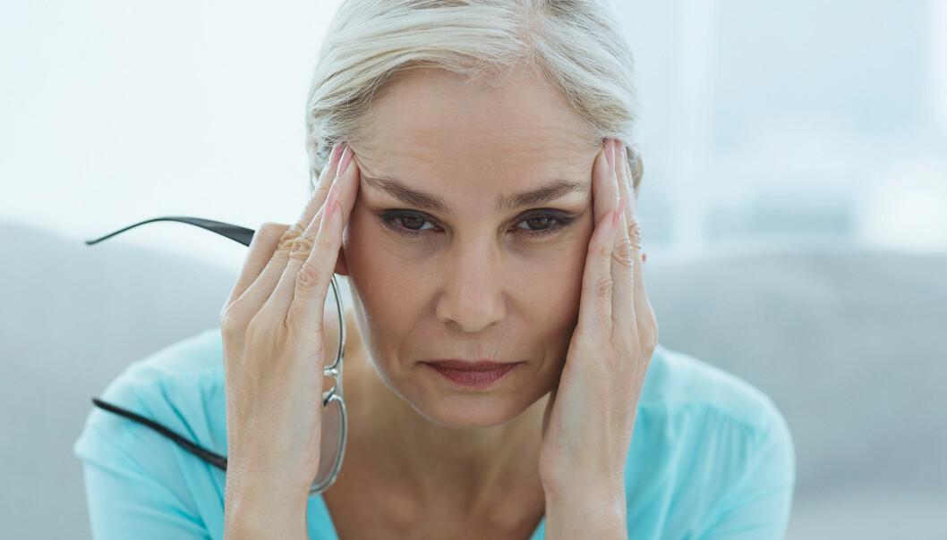 Stressad kvinna med ansiktet i händerna