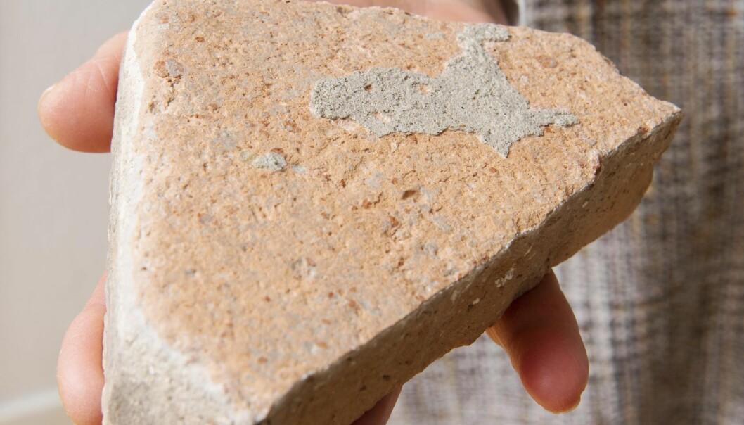 Tegelstensbit i handen från barndomshemsgolvet