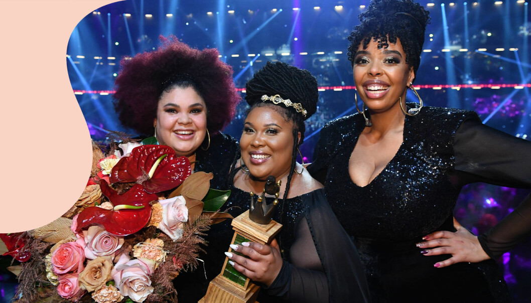 The Mamas vinner Melodifestivalen 2020 och poserar med vinnarstatyn och en stor blombukett.
