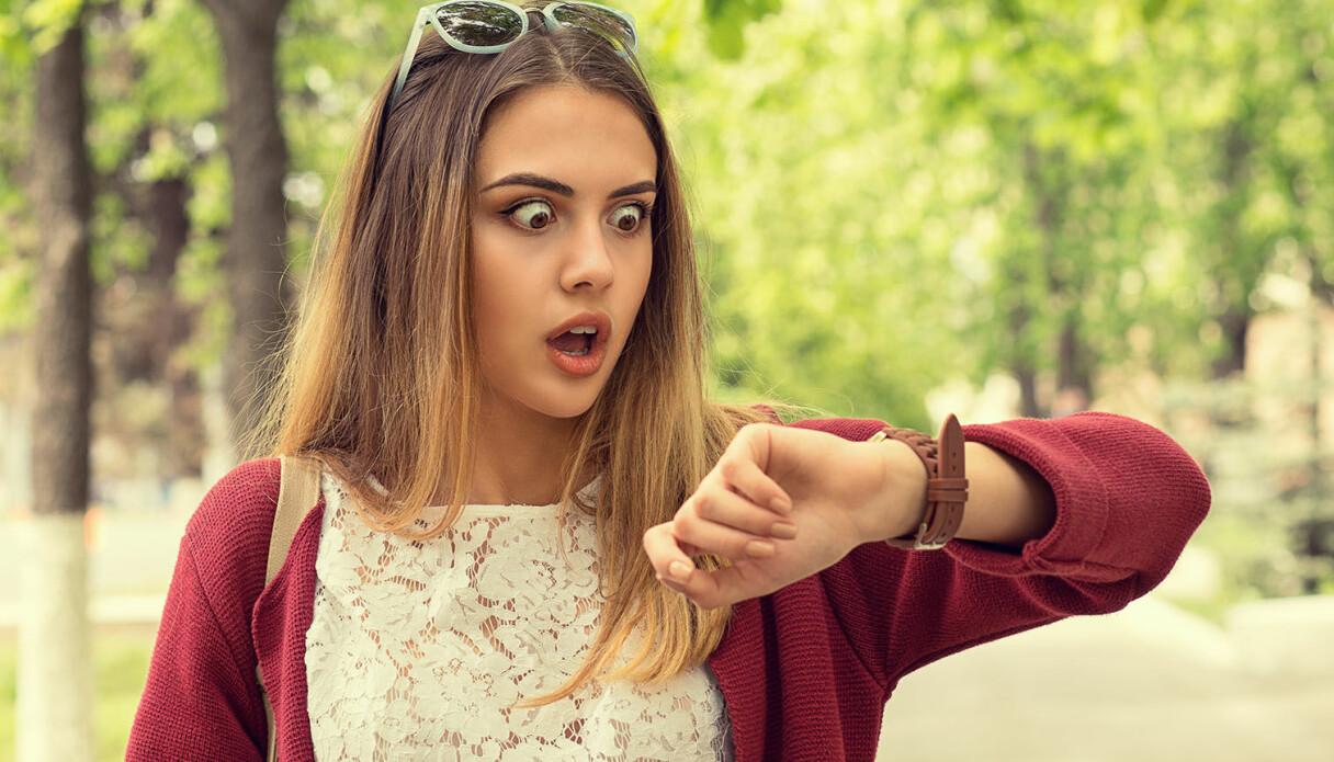 En tjej som stirrar på sin klocka och inser att hon är väldigt försenad.
