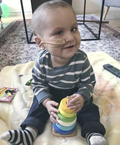 Tiger var fem månader gammal när han fick cancer. Här sitter han och leker samtidigt som han har en slang i näsan.