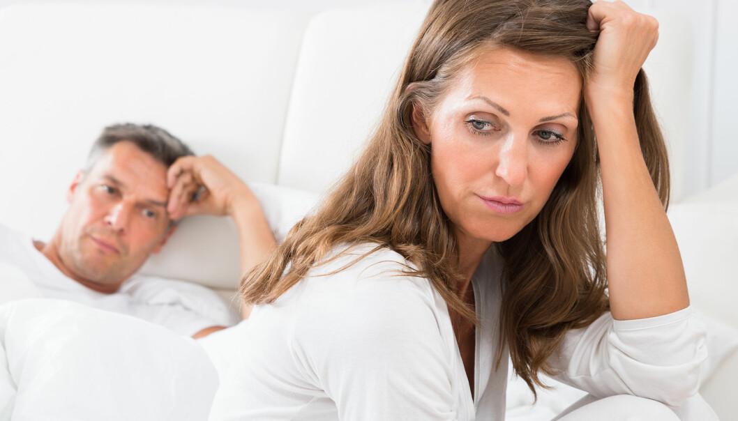 Kvinna och man ser uppgivna ut i en säng