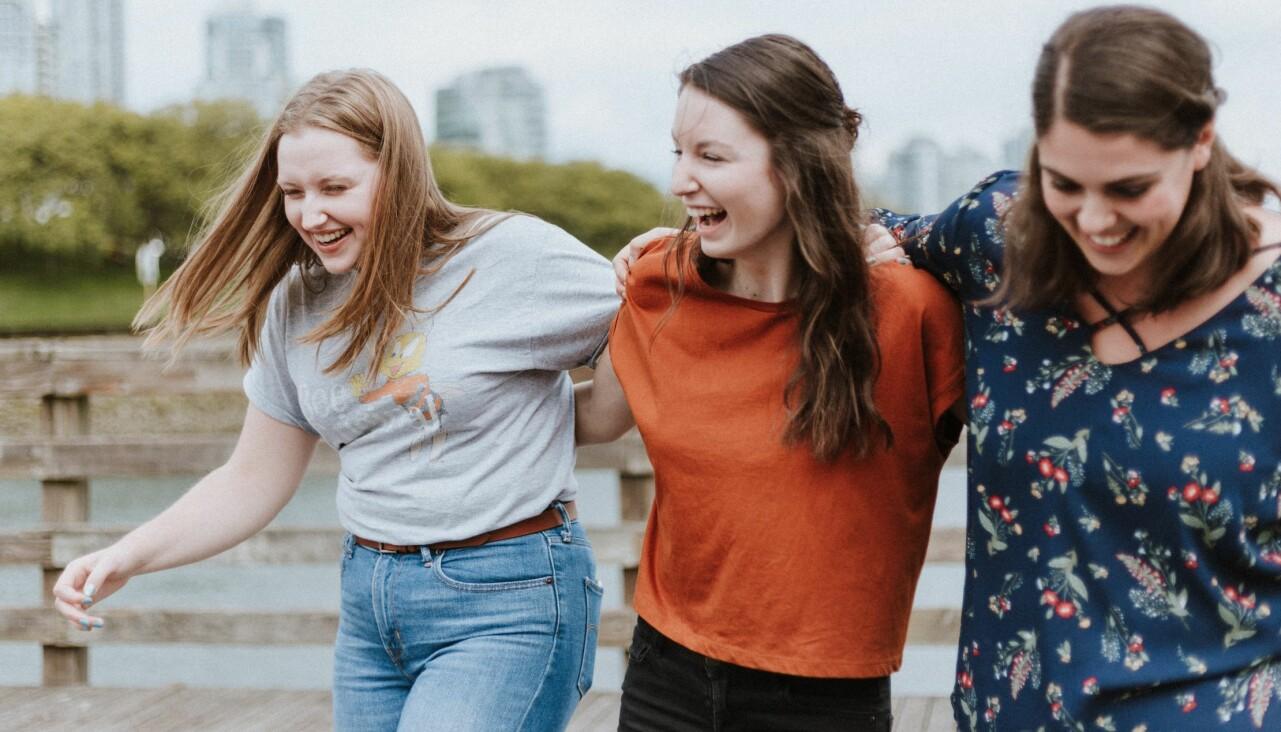 Tre glada vänner håller om varandra och skrattar.
