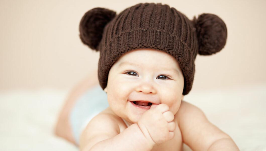 En bebis med en teddymössa skrattar in i kameran.