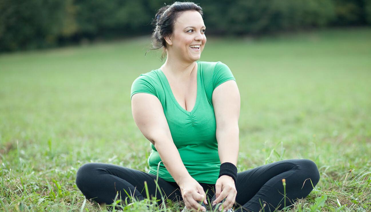Glad kvinna på gräsmatta.