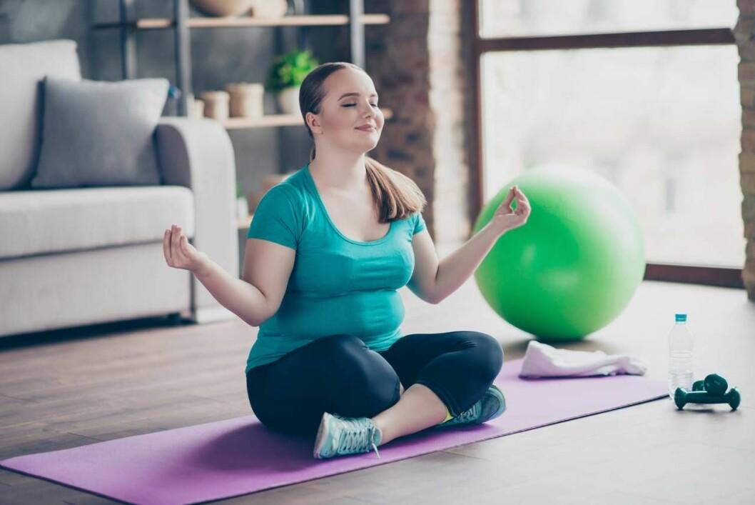 Kroppspositiv kvinna tränar yoga hemma
