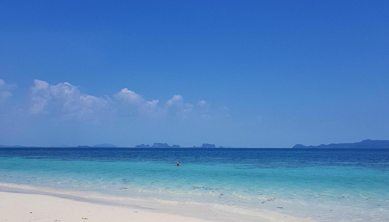 Turkosblått hav och vit slät sandstrand.