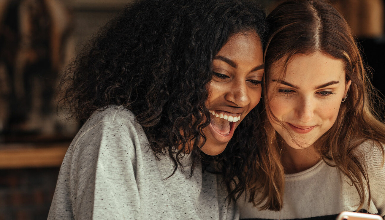 Två kvinnor kollar på en telefon ihop.