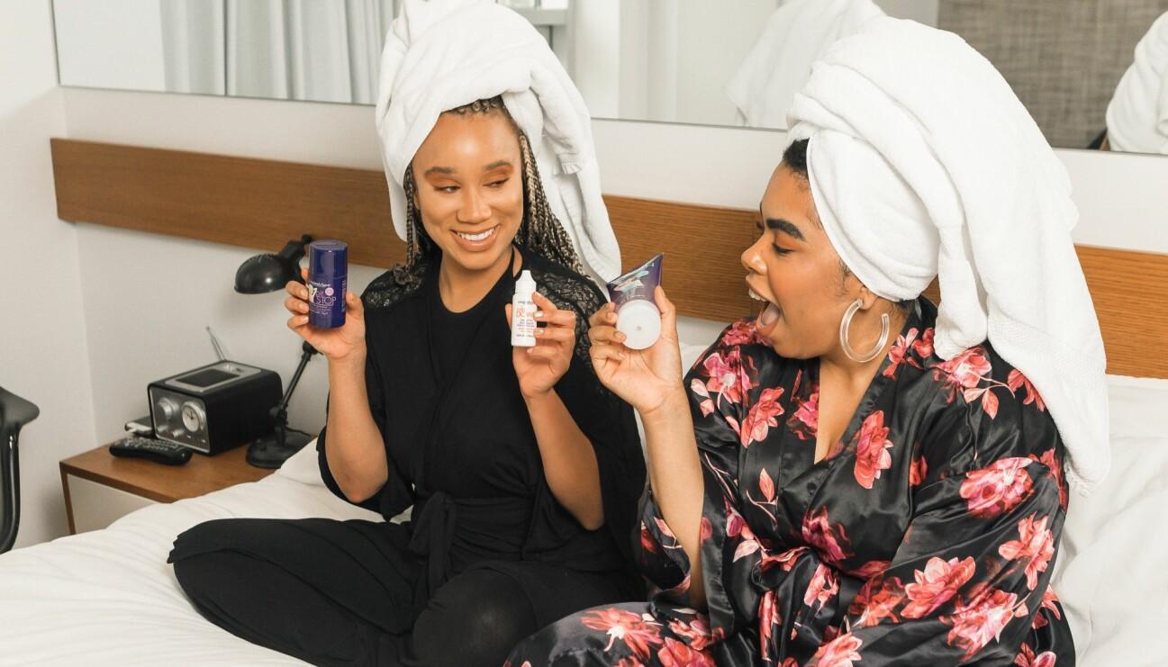 Två kvinnor sitter i en säng med diverse hudprodukter som de blivit lurade att sälja i en pyramidbluff.