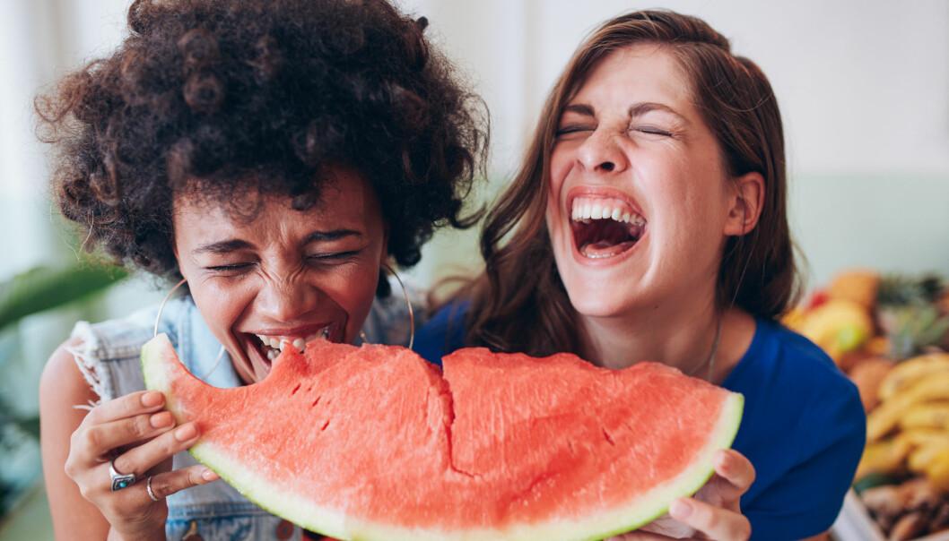 Två kvinnor skrattar medan de äter vattenmelon