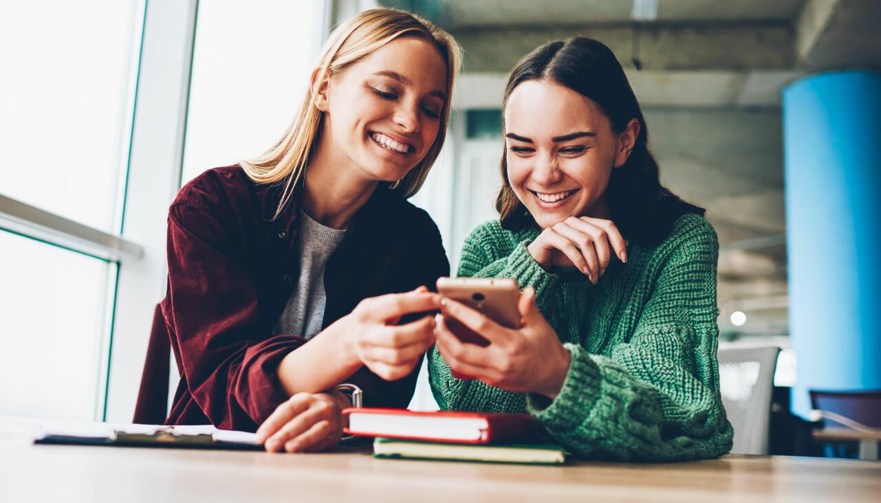 Två kvinnor tittar på en mobiltelefon och skrattar.