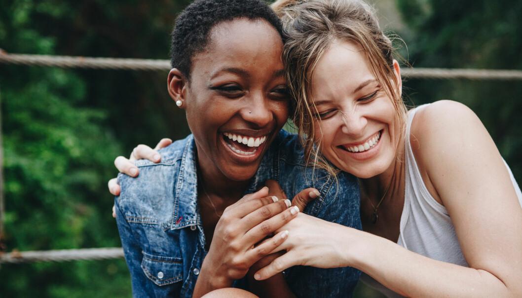 Två lyckliga och glada vänninor som håller om varandra.