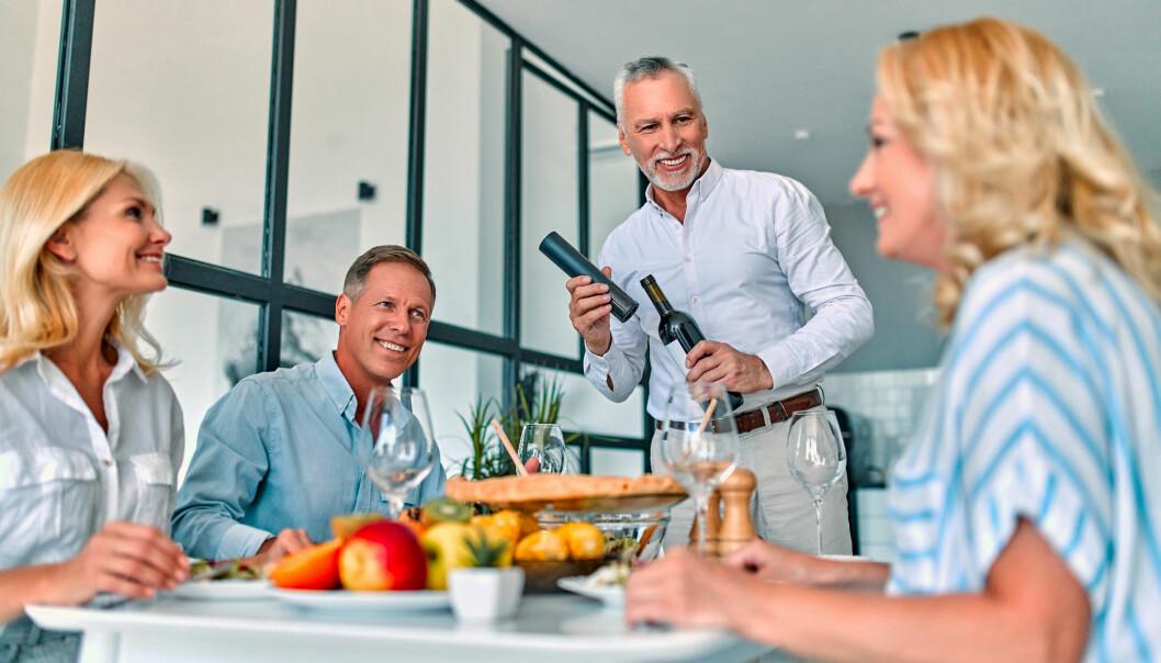 Två medelålders par umgås, dricker vin och har trevligt på parmiddag i fint hem.