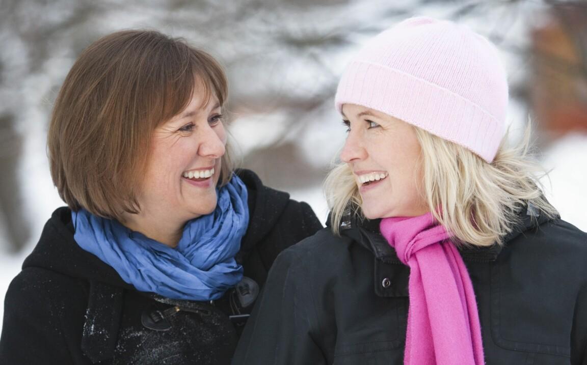 Två medelålders vänner tittar på varandra och ler stort.