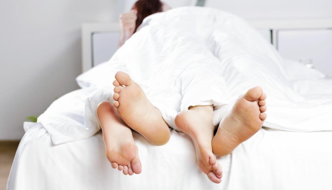 Två par fötter sticker fram under täcke.