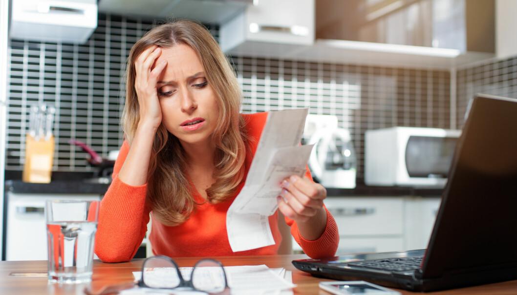 Ung kvinna sitter vid köksbordet för att betala sina räkningar och blir bekymrad över sin vardagsekonomi.