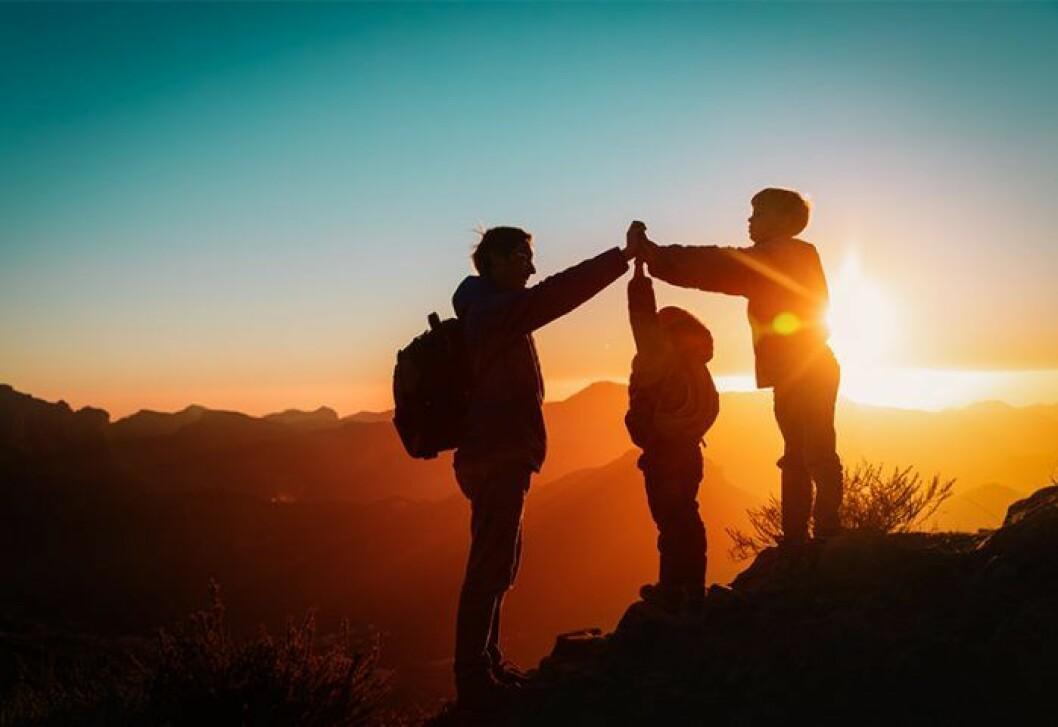Familj som är på vandring i solnedgång