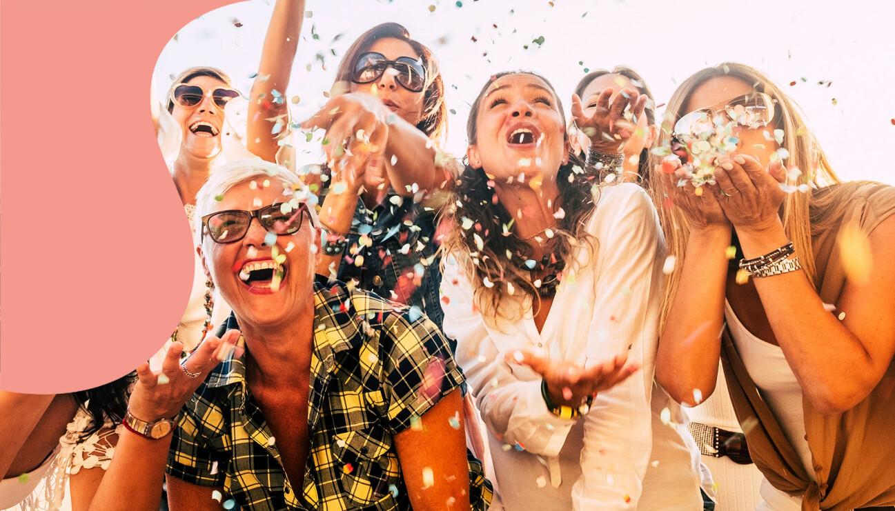Glada kvinnor blåser konfetti ut i luften.