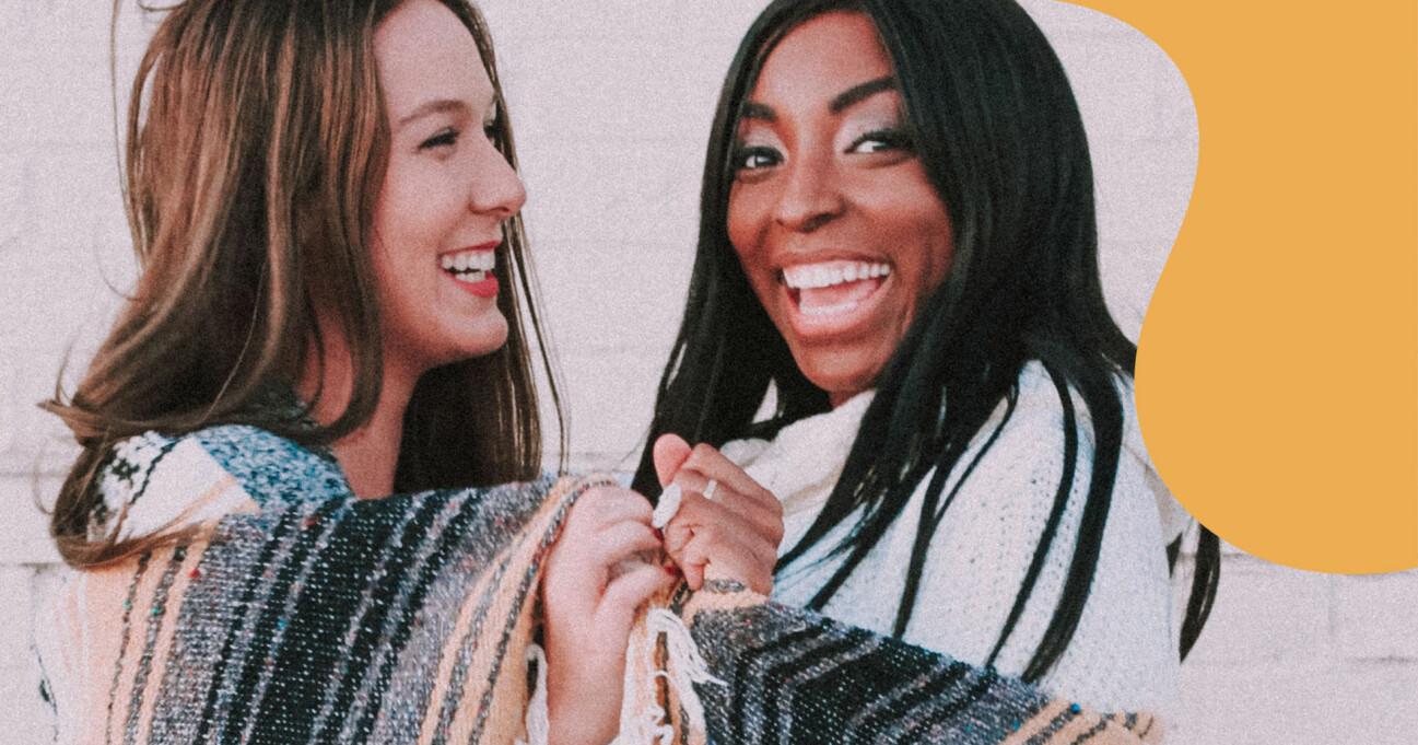 Två leende vänner skrattar tillsammans.