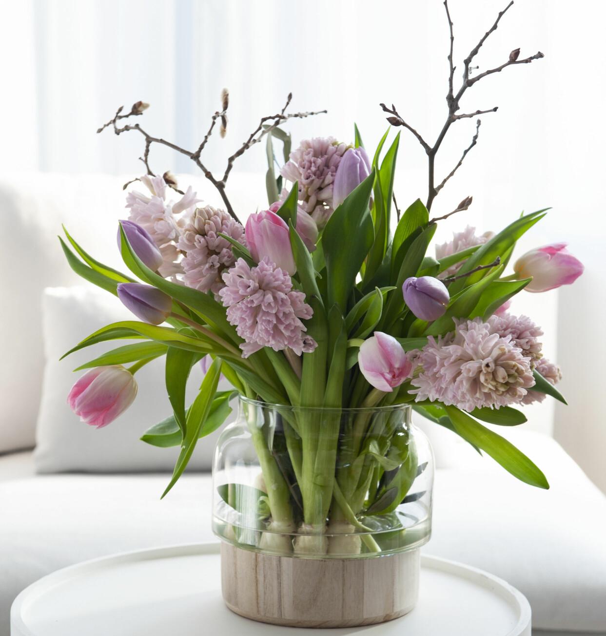 Vårbukett i rosa pastelltoner med tulpaner och kvistar.
