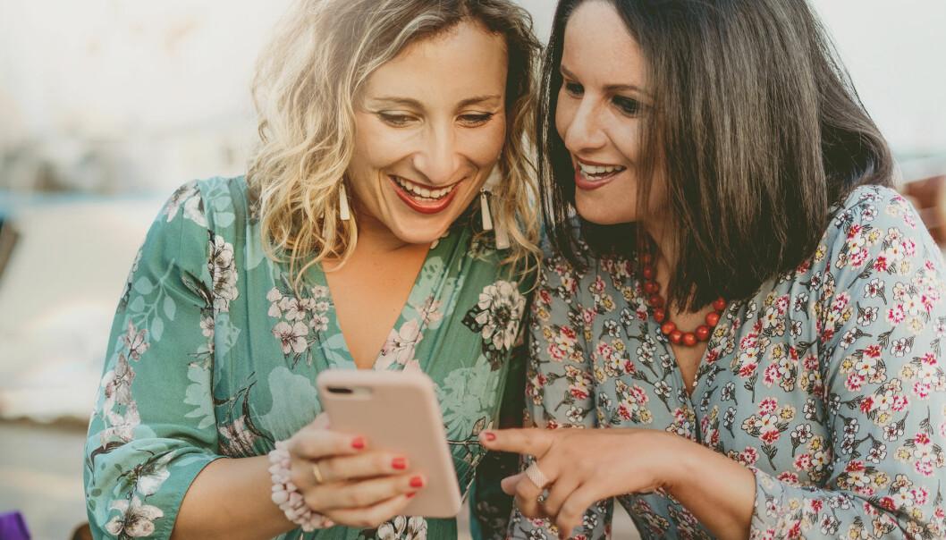 Kvinnor tittar i telefonen