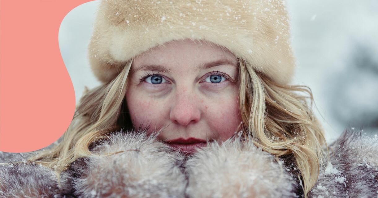 Leende kvinna i vinterkläder tittar in i kameran.