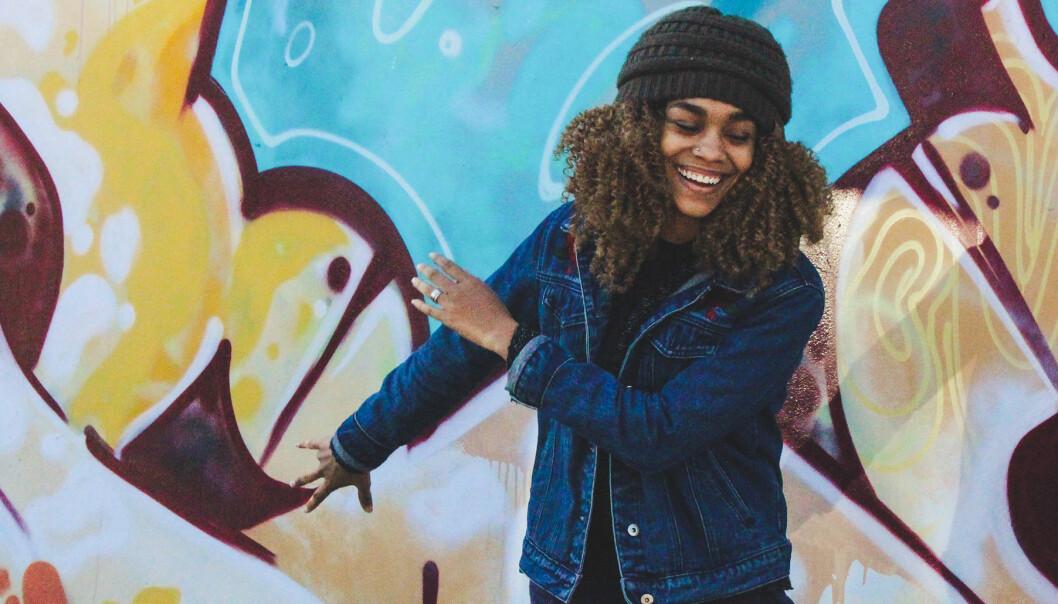 Kvinna i höstkläder framför en spraymålad vägg