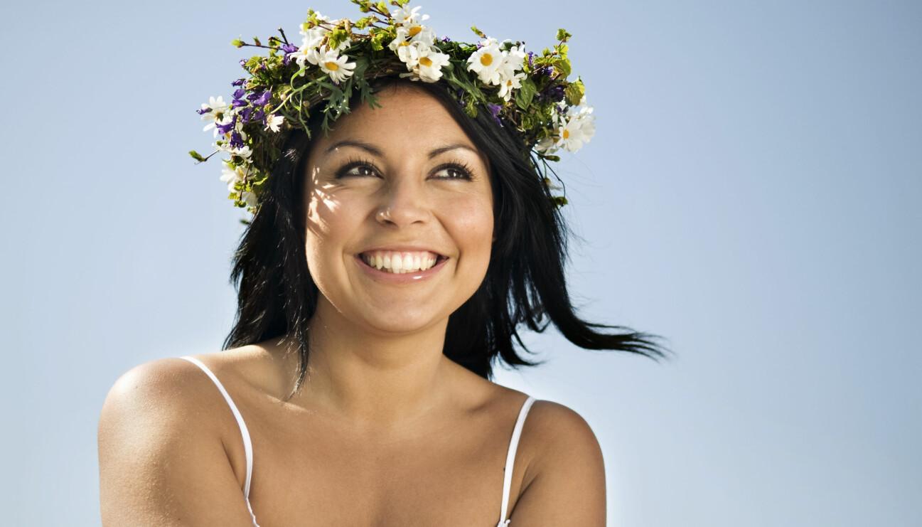 Leende kvinna med midsommarkrans i håret.