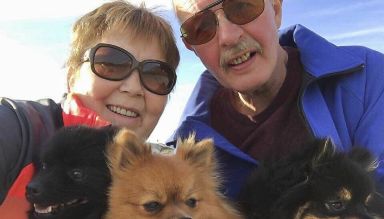 Ett äldre glatt och friskt par utomhus med sina hundar.