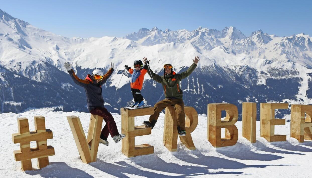 Johanna, Anders och Walter sitter på stora träbokstäver som formar namnet Verbier i en skidbacke.