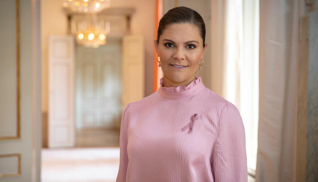 Kronprinsessan Victoria i rosa tröja med rosa bandet på.