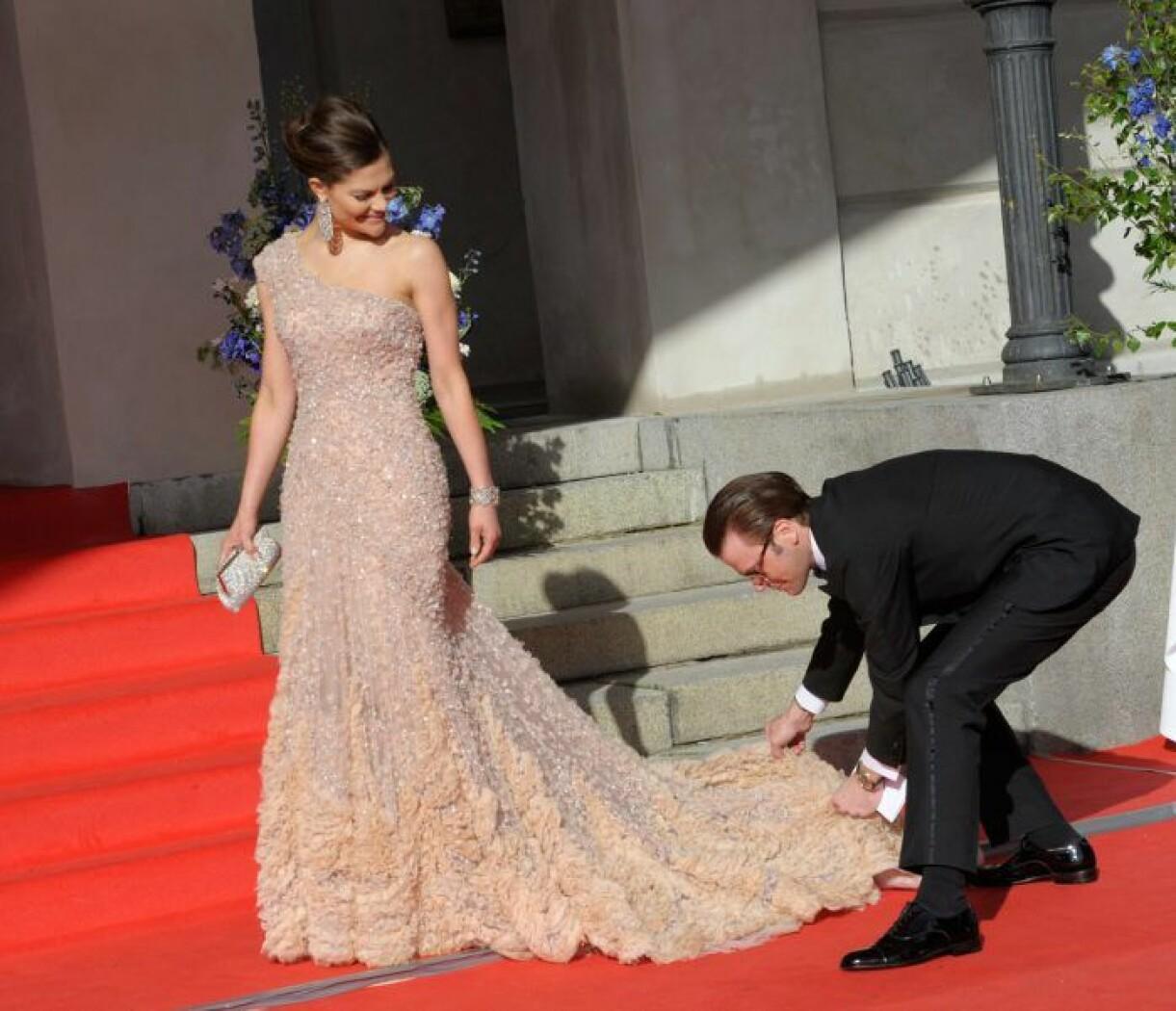 Prins Daniel rättar till kronprinsessan Victorias släp.