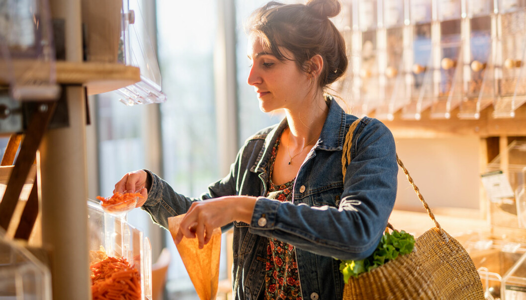 Kvinna i affär häller upp en vara i en papperspåse