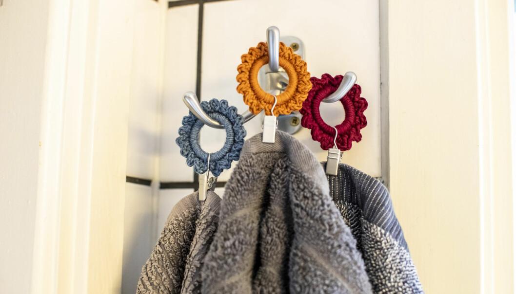 Tre virkade handdukshängare i grått, orange och vinrött hänger på en krok med gråa handdukar fastknipsade.
