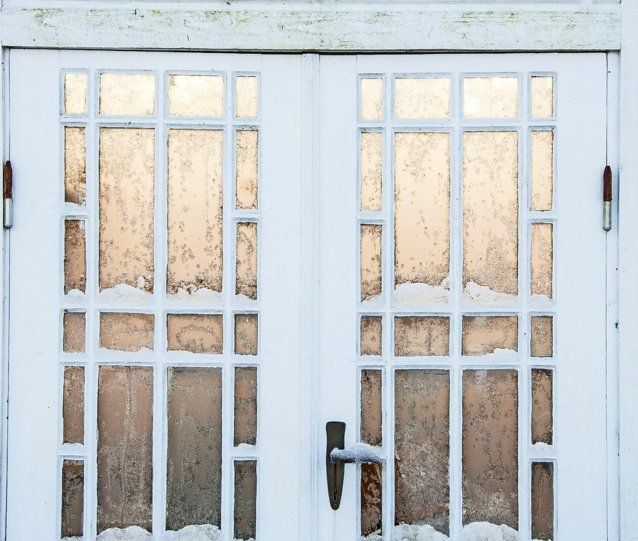 Vita växthusdörrar på vintern.