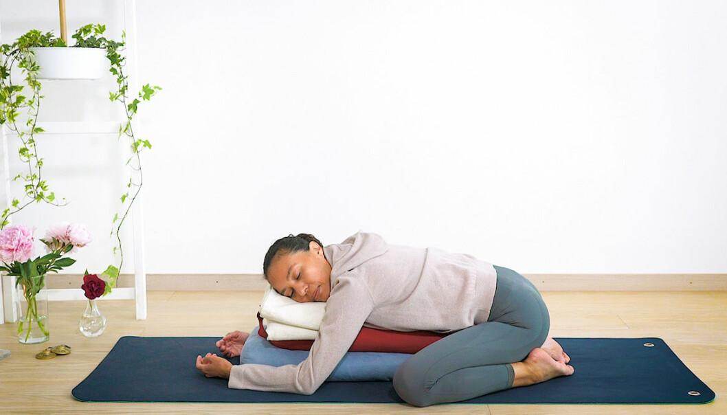 Yogainstruktör visar yogaövningar som hjälper dig med mensvärk och pms