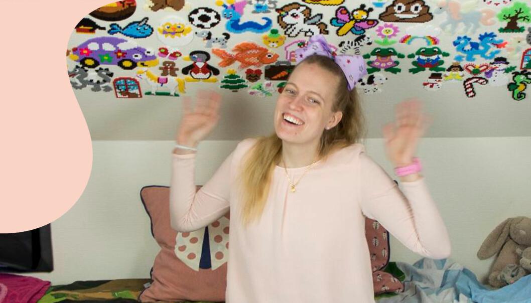 En glad Caroline på sitt rum där hon fotograferar och skriver på sociala media.