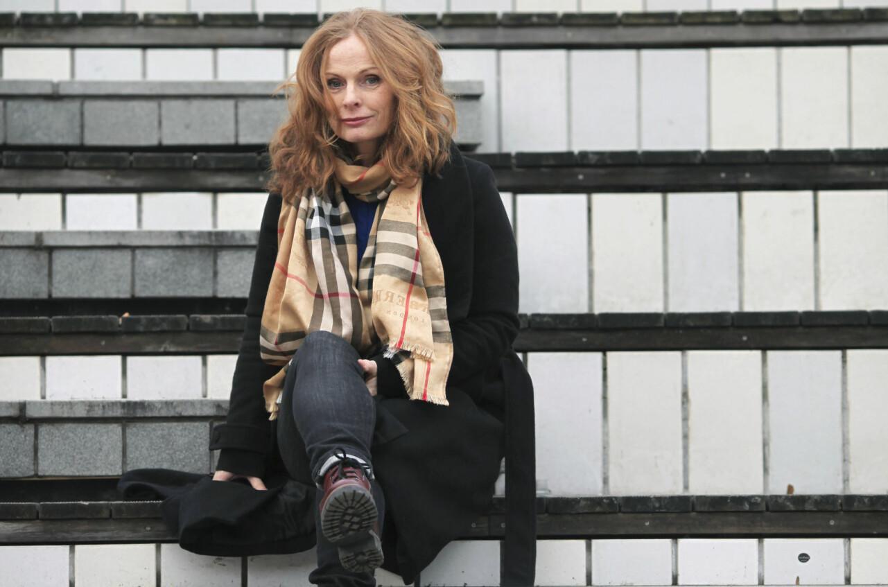 Yvette Westin, som blev shoppingberoende, poserar för en bild på en trappa.