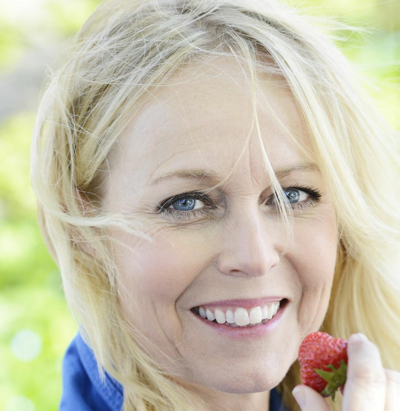 Porträtt på glad Annika med jordgubbe.